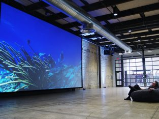 man watching large screen projector